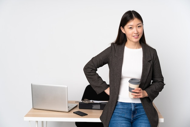 Business asian woman in her workplace on white wall in back position