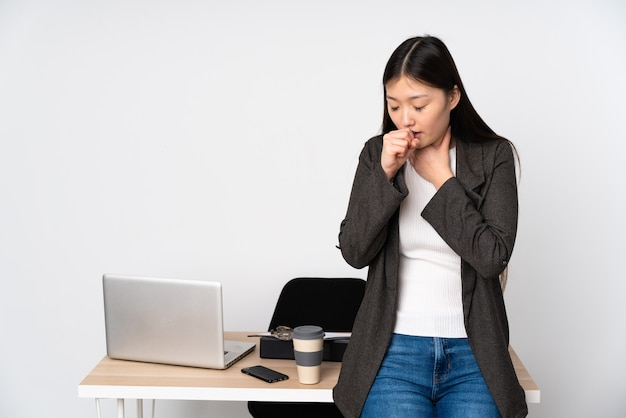 Business asian woman in her workplace on white wall is suffering with cough and feeling bad