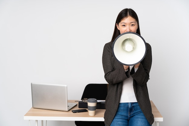 Business asian woman in her workplace on white wall shouting through a megaphone