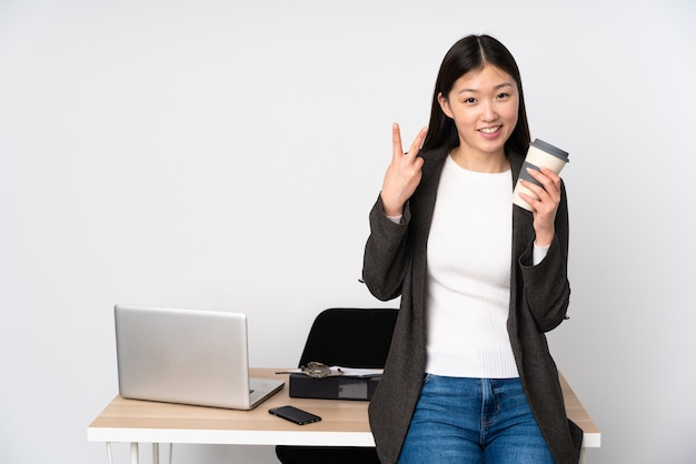 Business asian woman in her workplace on white wall showing victory sign with both hands