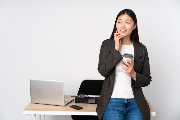 Business asian woman in her workplace on white wall thinking an idea while looking up