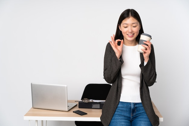 Business asian woman in her workplace on white wall in zen pose