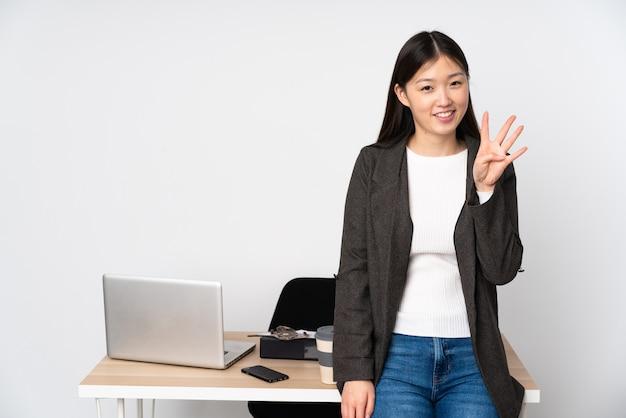 Женщина дела азиатская в ее рабочем месте изолированном на пустом пространстве счастливом и подсчитывать 4 с пальцами
