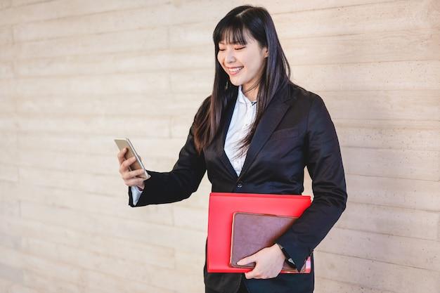 スマートフォンアプリを使用してオフィスビルからビジネスアジア女性-仕事に行く若い女性労働者-技術、起業家、仕事のコンセプト-彼女の顔に焦点を当てる