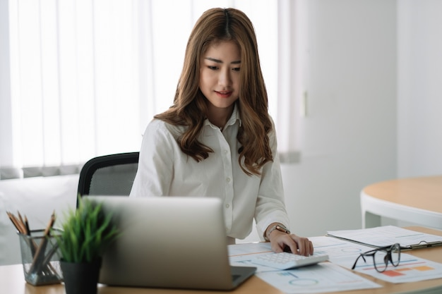 재무 보고서 작업에서 계산기를 사용하는 비즈니스 아시아 여성. 그녀는 노트북 컴퓨터로 작업.