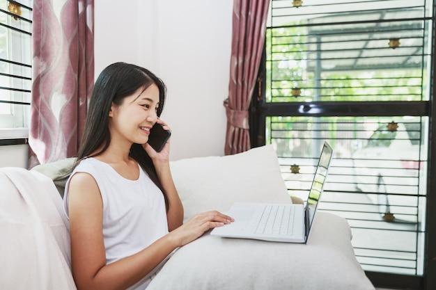 自宅のソファで携帯電話とラップトップコンピューターで作業アジアのビジネス女性