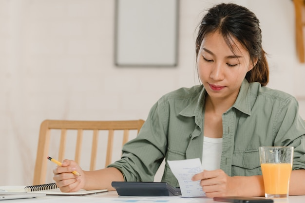 Business asian women records of income and expenses at home