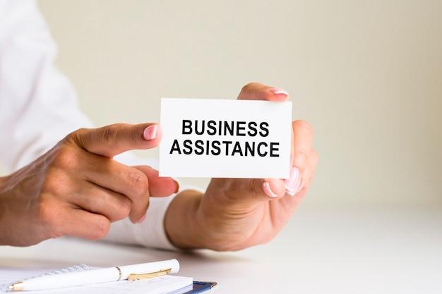 Надпись помощи бизнесу на листе бумаги белой карточки в руках женщины. черные и красные буквы на белой бумаге. бизнес-концепция, серый фон