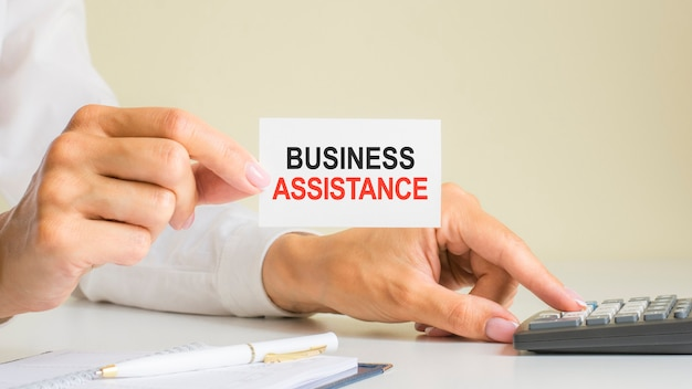 Деловая помощь, сообщение на визитной карточке, показанной женщиной, нажимающей клавишу калькулятора на рабочем месте в светлом офисе, выборочный фокус, бизнес и финансовая концепция