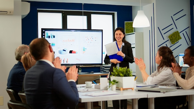 여성 리더 관리자에게 박수를 보내는 비즈니스 청중은 회의 세미나, 디지털 차트 프레젠테이션에 감사함을 표시하고, 다민족 사무실 사람들이 박수를 치고 교육 연사 개념을 칭찬합니다.