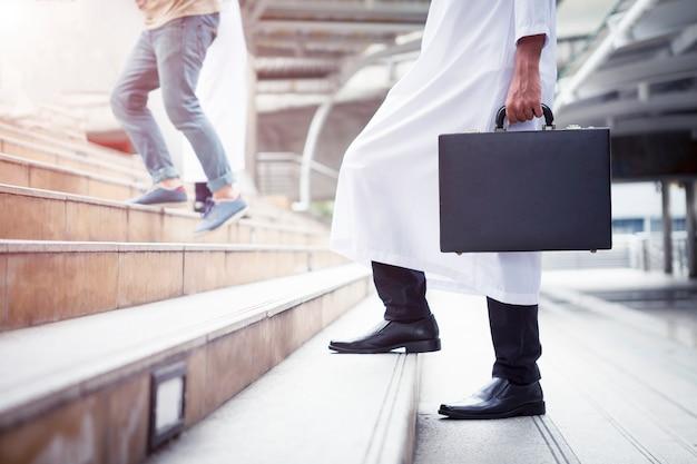 ビジネスの背景のコンセプト。アラブのビジネスマン、ビジネスバッグ、階段を上って歩く