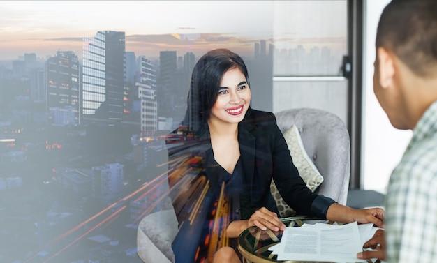 자카르타 도시 경관을 통해 남자와 상담하는 인도네시아 여성과 사업 배경