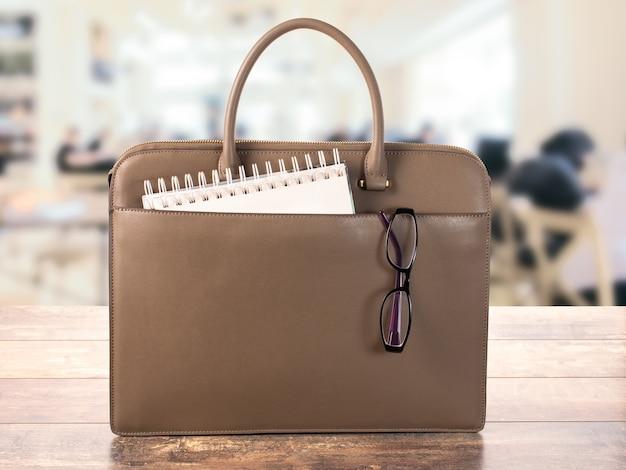 メガネとメモ帳付きのビジネスバッグ。オフィスワークやトレーニングの概念、オフィススペースのぼやけた背景に関する教育