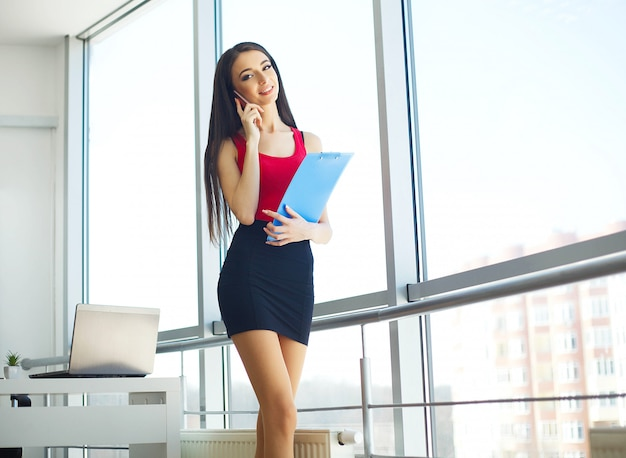 Business. beautiful woman speaks by phone. works in the light office and holding the folder in their hands