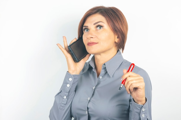Business beautiful woman speaks on the phone with a pen in her hand