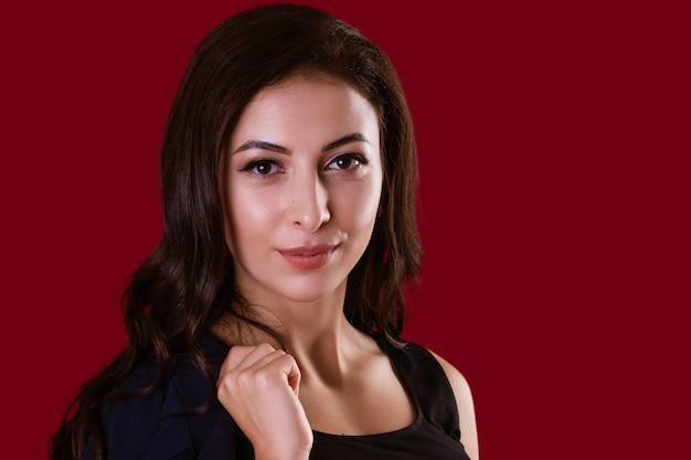 Business beautiful woman in suit posing on red background