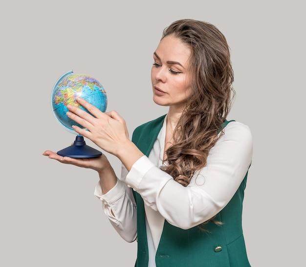 그녀의 손에 글로브와 비즈니스 아름 다운 여자는 전 세계에 지점을 가리 킵니다.