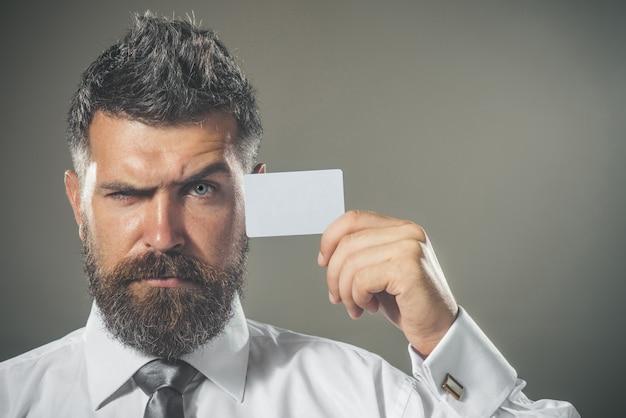 비즈니스 브랜딩 사업가 손에 빈 비즈니스 카드와 함께 심각한 수염 난된 남자는 신용 카드를 보여줍니다