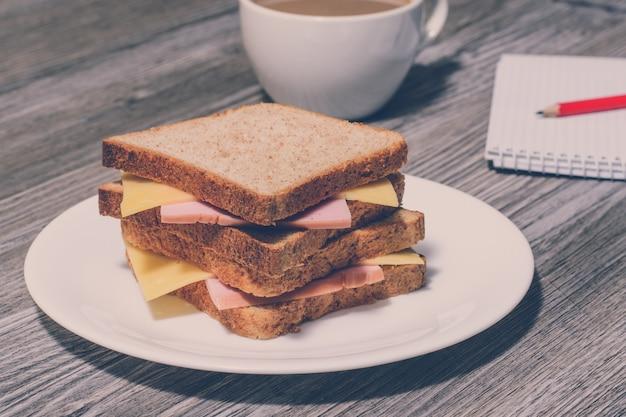 ビジネス朝食。一杯のコーヒー、ノート、鉛筆でおいしいハムとチーズのサンドイッチ。灰色の木製の背景、ヴィンテージ効果