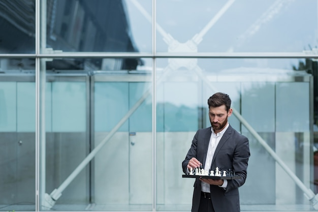 Business broker man standing near office holding board with playing chess, thinking about business strategy