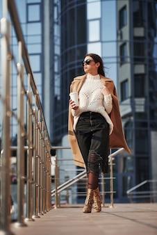 背後にあるビジネスビル。暖かい服を着た美しい少女は、彼女の週末の時間に街を歩いています。