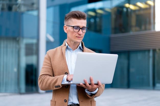 Бизнес. бизнесмен используя ноутбук открытый взрослый кавказский мужской деловой человек очки наблюдая экран ноутбука за пределами серьезного мышления солнечного фона улицы большого города