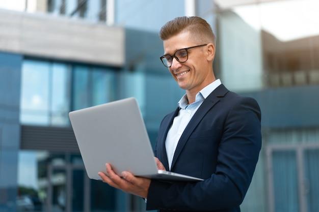 Бизнес. бизнесмен используя ноутбук открытый взрослый кавказский мужской деловой человек очки наблюдая экран ноутбука за пределами улыбаясь счастливые положительные эмоции фон солнечного света улицы большого города