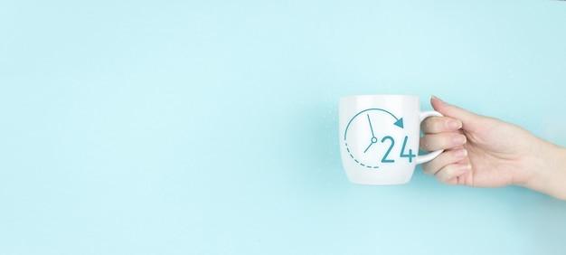 Деловая кнопка круглосуточное обслуживание. девушка рукой держать утреннюю кофейную чашку с знаком 24-часовой значок на синем фоне. концепция полного рабочего дня