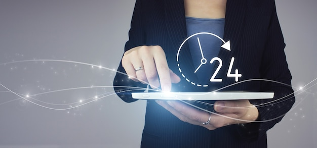 Business button 24 hours service. white tablet in businesswoman hand with digital hologram 24/7 all day all night icon on grey background. full time service concept