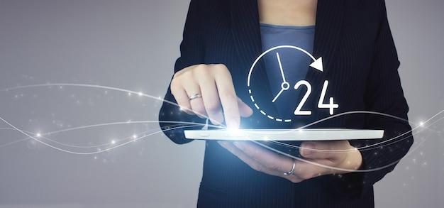 비즈니스 버튼 24시간 서비스. 회색 배경에 하루 종일 밤새도록 디지털 홀로그램 아이콘이 있는 사업가 손에 흰색 태블릿. 풀 타임 서비스 개념