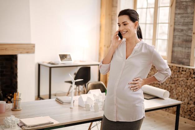 ビジネスコール。電話とニヤリとしながら腹に手を置くうれしいポジティブな妊娠中のデザイナー