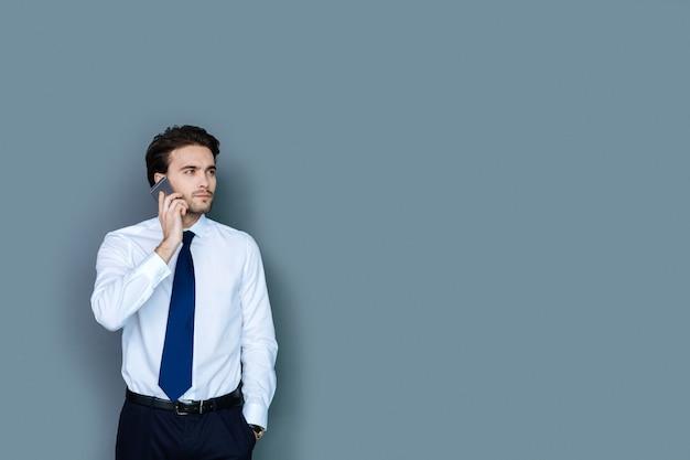 ビジネスコール。スマートフォンを持ってオフィスで働いている間電話をかけるスマートな素敵な自信のある男
