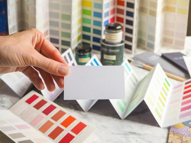 Визитная карточка и большая палитра цветов. выберите цвет из широкого спектра эмали краски.
