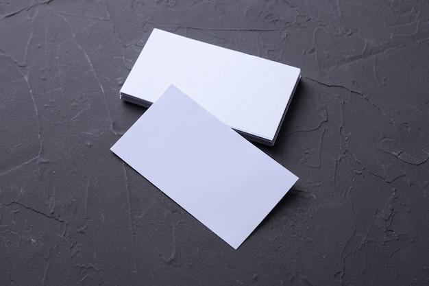ベトンロックの背景に空白の名刺。コーポレートステーショナリー、ブランディングモックアップ。クリエイティブデザイナーデスク。フラットレイ。テキスト用のスペースをコピーします。 idのテンプレート。