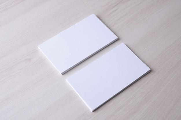 Пустая визитная карточка на деревянных фоне. креативный дизайнерский стол. плоская планировка. скопируйте место для текста.