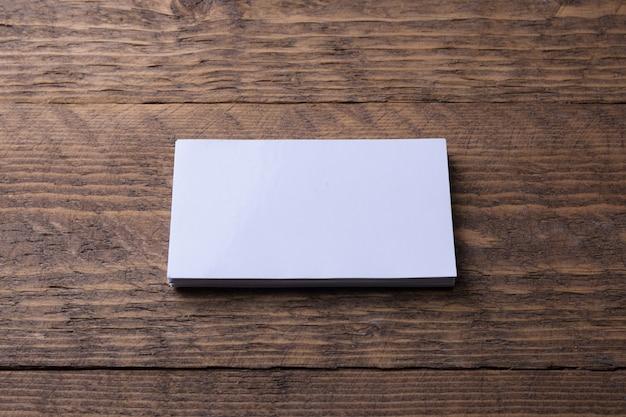 木製の壁に空白の名刺。コーポレートステーショナリー、クリエイティブデザイナーデスク。フラットレイ。テキスト用のスペースをコピーします。