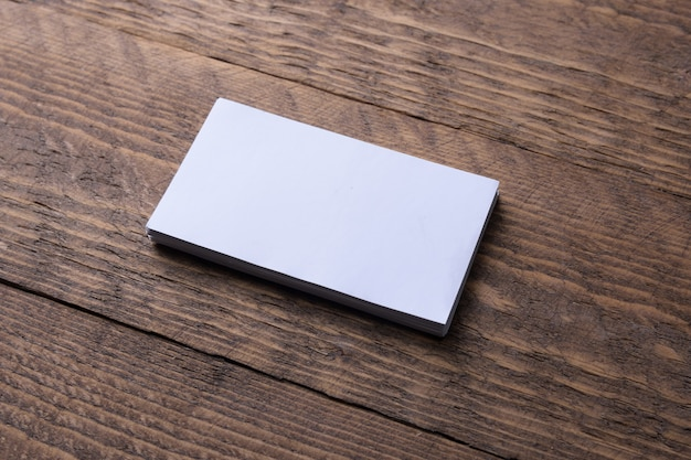 Business card blank on wooden background. corporate stationery, branding mock up. creative designer desk. flat lay. copy space for text. template for id.
