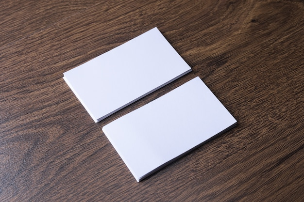Business card blank on wooden background. corporate stationery, branding mock-up. creative designer desk. flat lay. copy space for text. template for id.