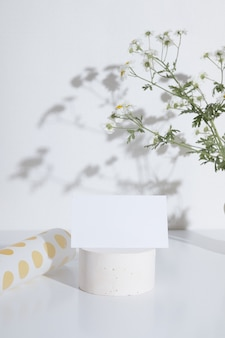 Business card or invitation mockup on a pedestal with a branch of chamomile. fashionable creative for the cosmetic business