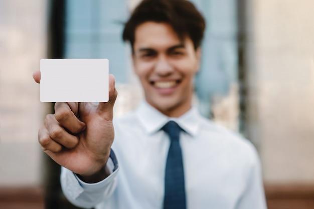 名刺のモックアップ画像。クリッピングパスを持つ白い空白の紙カードを提示する幸せな青年実業家