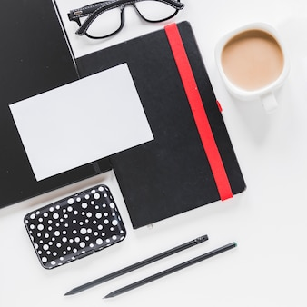 Business card on notebook and coffee cup near case and glasses