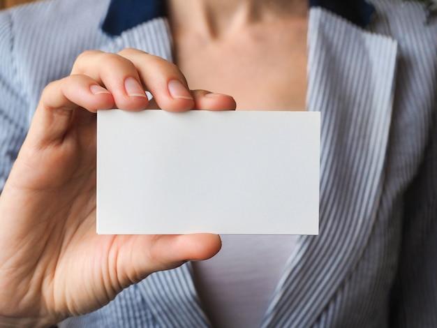 Визитная карточка с копией пространства в руке крупным планом.