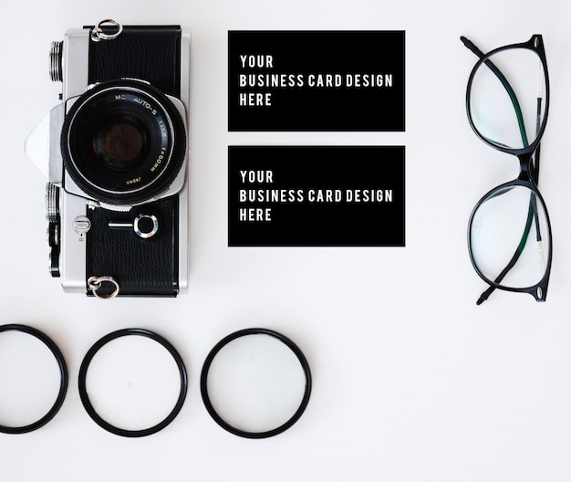 Business card with old film camera and lenses with filters and glasses