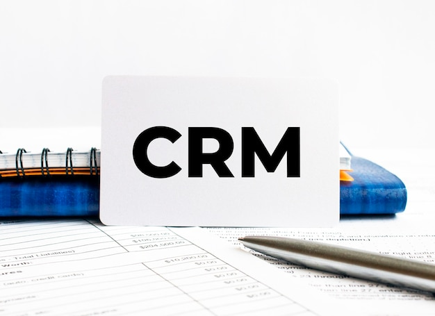 Business card with text crm lying on blue notebook,concept