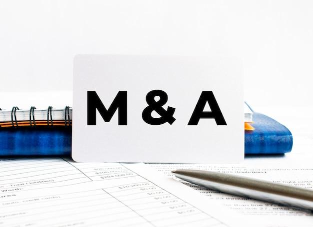 Визитная карточка с текстом m и a, лежащим на синем блокноте, концепция
