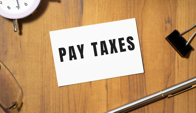 A business card with the text pay taxes lies on a wooden office table among office supplies
