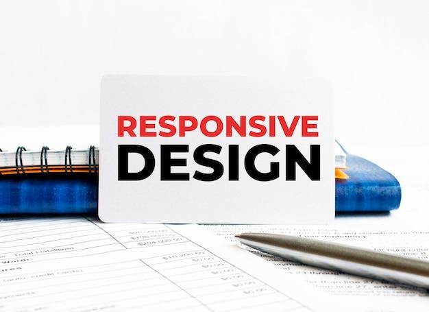 青いノートに横たわっているテキストレスポンシブデザインの名刺。 Premium写真