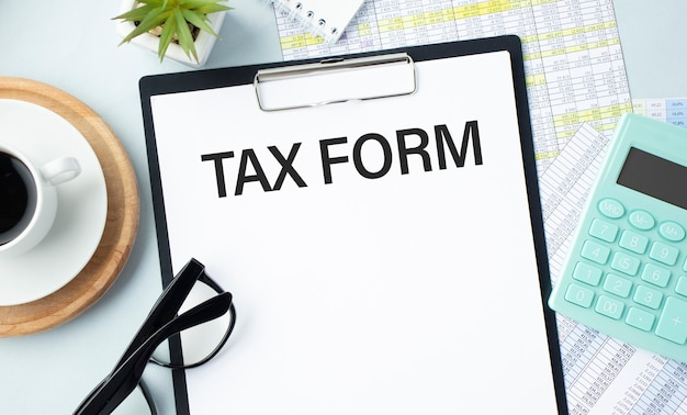 The business card with the text tax form is on the financial documents. calculator and pen. can be use as a financial and business concept