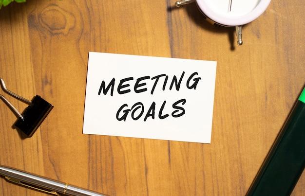 텍스트 회의 목표와 명함은 나무 사무실 테이블에 놓여 있습니다.