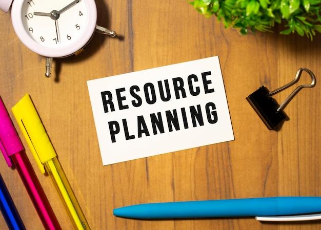 Визитная карточка с текстом планирование ресурсов лежит на деревянном офисном столе.